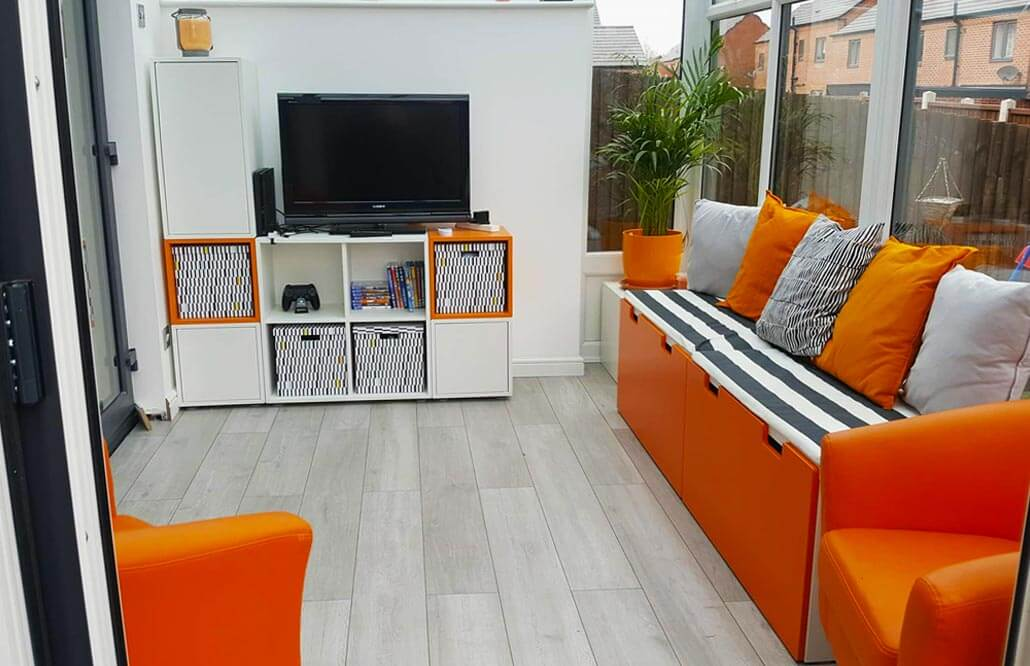 Interior of a modern conservatory with orange accented furniture.